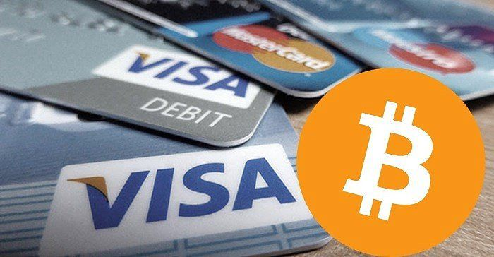Picture of a bitcoin logo with Visa and MasterCard debit cards behind it