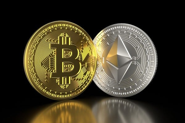 Picture of two crypto coins, a gold bitcoin and a silver ethereum, standing side by side