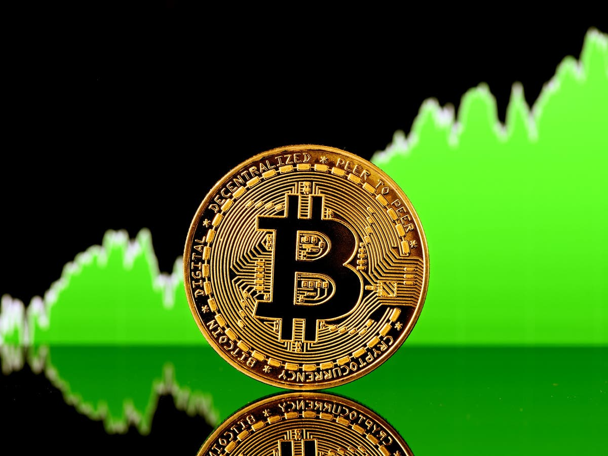 Picture of a bitcoin with a green upward chart behind it